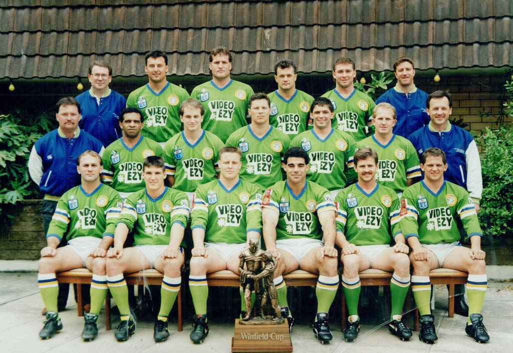 1990 Grand Final Winners: Lazarus sits next to co-captain Mal Menings (current QLD coach) while Laurie Daley (current NSW coach) sits in the back left. Current Raiders coach Ricky Stuart sits back right.