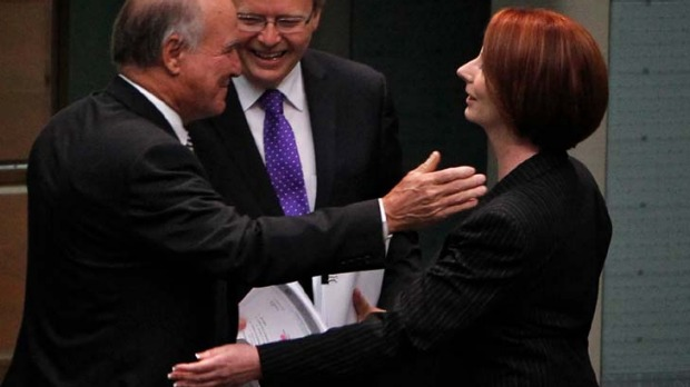 Julia Gillard embraces Independent MP Tony Windsor as Kevin Rudd looks